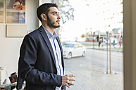 Serious young businessman looking out of window - JASF000364