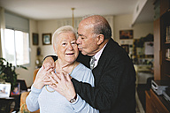 Senior couple hugging and kissing at home - GEMF000670