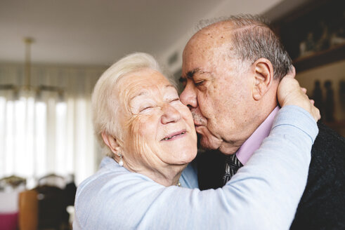 Senior couple hugging and kissing at home - GEMF000673