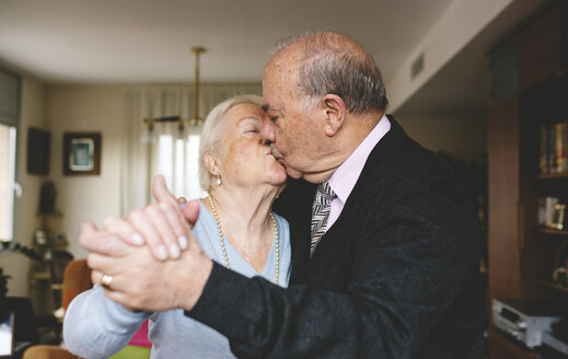 Senior couple kissing and dancing at home - GEMF000676