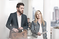 Man with briefcase and woman with construction plan talking in office - ZEF008166