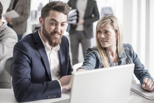 Man and woman in office looking at laptop - ZEF008184