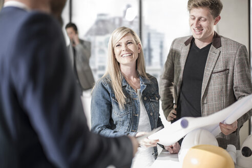 Smiling colleagues in office with construction plan - ZEF008190