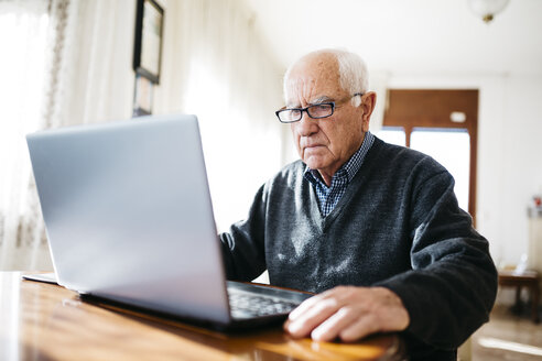 Portrait of serious looking senior man using laptop at home - JRFF000356