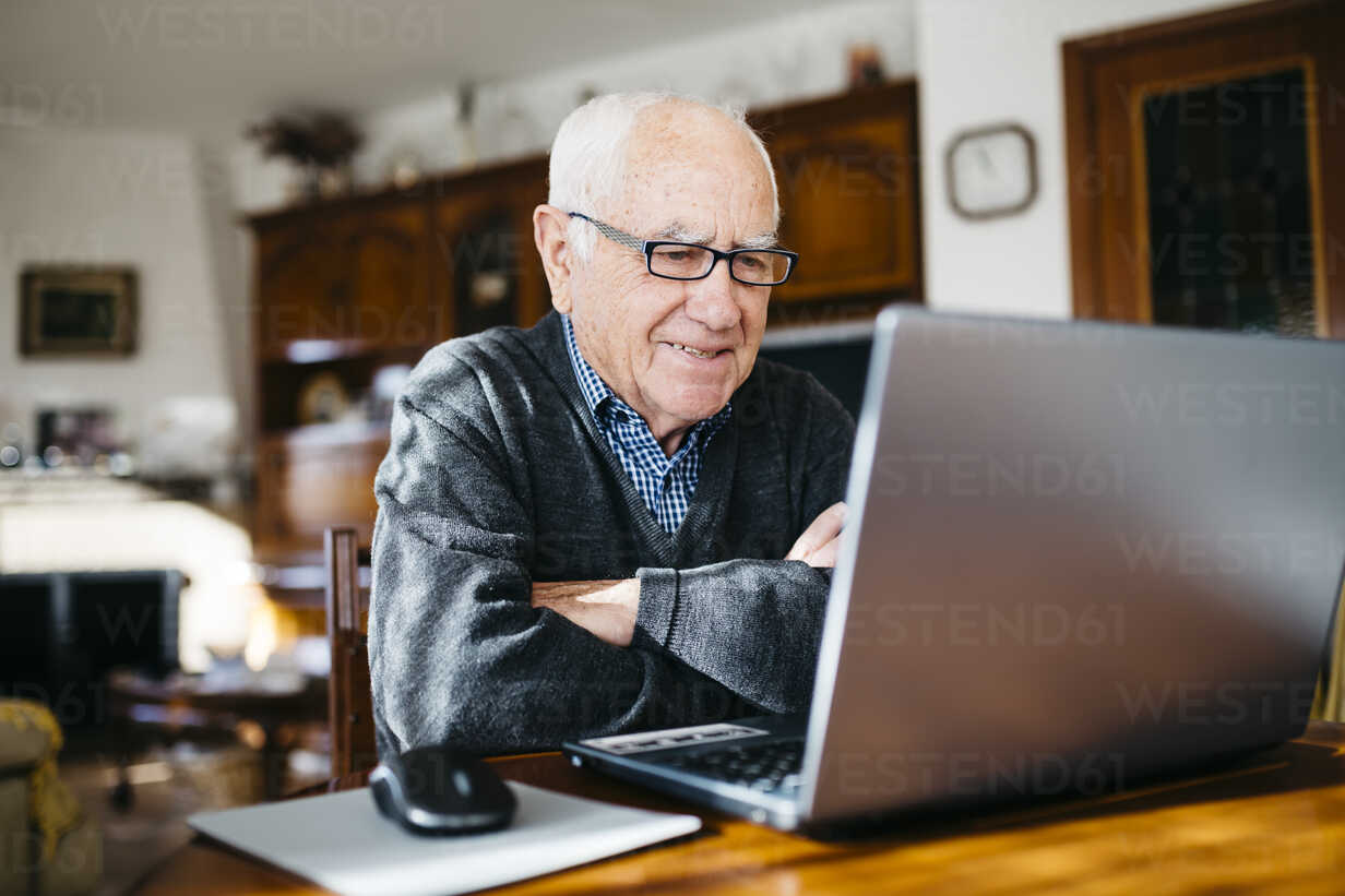 Portrait of smiling senior man with laptop at home - JRFF000362 - Josep Rovirosa/Westend61