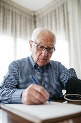 Senior man controlling his blood pressure and writing down the result - JRFF000371