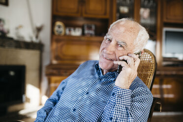 Portrait of smiling senior man telephoning with smartphone at home - JRFF000383