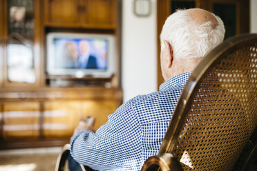 Back view of senior man sitting in his rocker watching television - JRFF000386