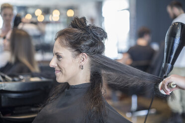 Woman in hair salon getting hair dried - ZEF008208