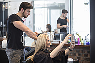 Woman in hair salon checking hairstyle in mirror an taking selfie - ZEF008217