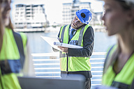 Engineer on construction site holding blueprint, talking on the phone - ZEF008241