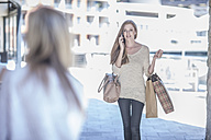 Woman with shopping bags talking on the phone - ZEF008265