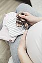 Pregnant woman holding baby's socks - VTF000492