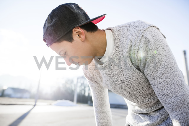 Young man wearing basecap in backlight - DAWF000494