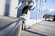 Low section of young man doing a trick on inline skates - DAWF000503