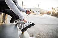 Close-up of young man putting on inline skates - DAWF000506