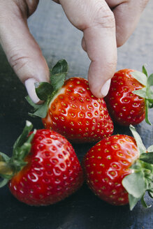 Fingers taking a strawberry - ABZF000183