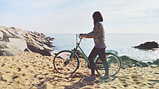 Barcelona, Spain. Woman pushing a bicycle through the sand on the beach - GEM000678