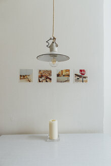 Row of four polaroids on a wall, old ceiling light and a candle on table top - JUBF000080