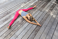 Woman in yoga straddle position on deck - KNTF000221