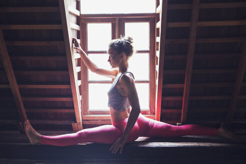 Woman in yoga position in attic - KNTF000224