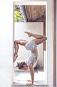 Woman doing a handstand in doorframe - KNTF000227