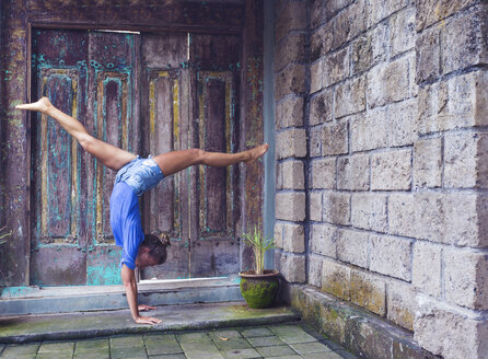 Woman doing a handstand outdoors - KNTF000230