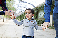 Portrait of happy toddler walking hand in hand with his parents - VABF000109