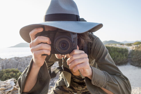 Spain, Ibiza, photographer wearing floppy hat taking a picture - NDF000568