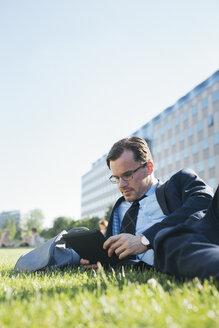 Businessman resting on meadow looking at digital tablet - JUBF000085