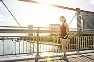 Germany, Frankfurt, young athlete stretching on bridge - PUF000468