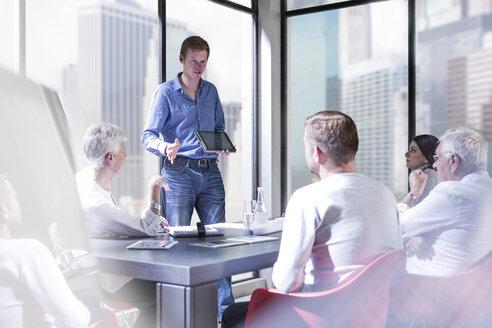 Man showing digital tablet in business meeting - ZEF008327