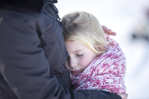 Girl cuddling with her mother in winter - ASCF000480