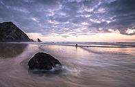 Portugal, Praia da Adraga, surfer on beach at sunset - STCF000186