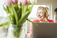 Smiling senior woman sitting at table with laptop - UUF006427