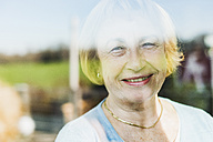 Portrait of smiling senior woman behind windowpane - UUF006448