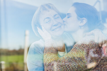 Young woman kissing senior woman behind windowpane - UUF006451