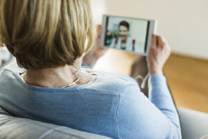 Senior woman looking at picture of young man on digital tablet - UUF006463