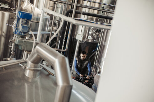 Young man working in craft brewery - ZEDF000039