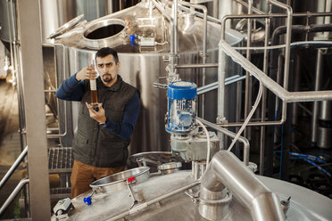 Young man working in craft brewery - ZEDF000045