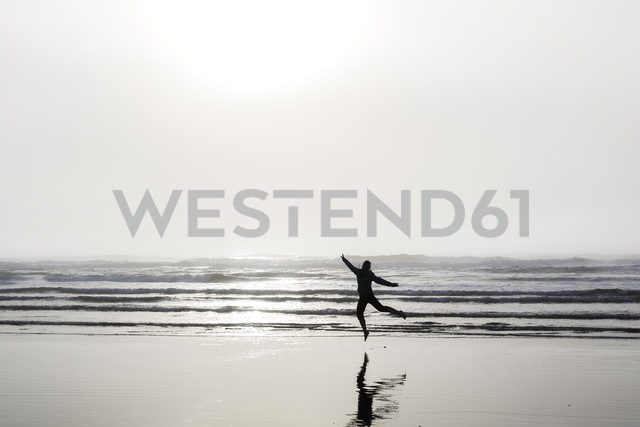 USA, Washington State, woman jumping on Long Beach - NGF000261