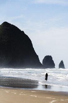 USA, Oregon, Cannon Beach, Haystack Rock, woman on the beach - NGF000264