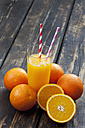 Whole and sliced oranges and glass of orange juice on wood - CSF027026