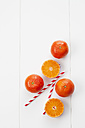 Whole and sliced tangerines and two drinking straws on white ground - CSF027065