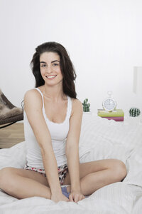Portrait of smiling young woman sitting on bed - GDF000959