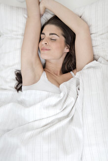 Smiling young woman sleeping in bed - GDF000962