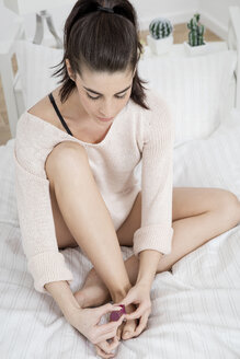Young woman on bed painting her toenails - GDF000965
