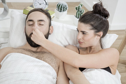 Couple lying in bed with man snoring - GDF000968