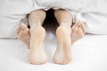 Feet of couple having sex in bed - GDF000971
