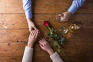 Hands of a young couple with red rose and a bottle of white wine - HAPF000174